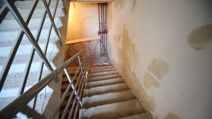 Driving downwards on stairs of under construction house to