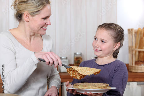 A mother cooking crepes with her daughter.