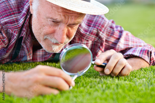 Close up of senior gardener cutting grass