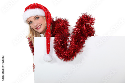 Festive woman stood with blank poster