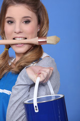 woman painter holding brush between teeth