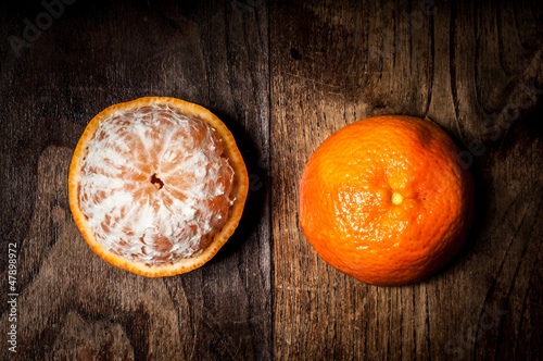 peeled mandarin with leaf on wood