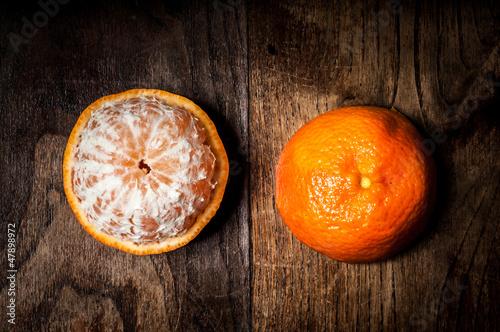 peeled mandarin with leaf on wood