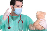 Man dressed as a surgeon quarrelling with teddy bear