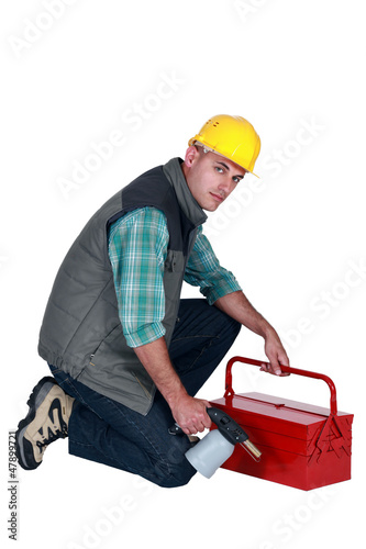 Workman with a blowtorch and toolbox