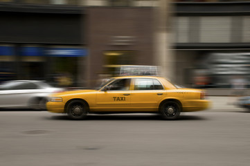 Blurred taxi speeding on city street