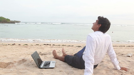 Happy businessman relaxing at beach while summer holiday