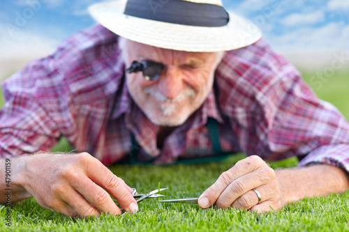 Close up of senior gardener cutting grass 3
