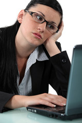 Pensive woman in front of her computer