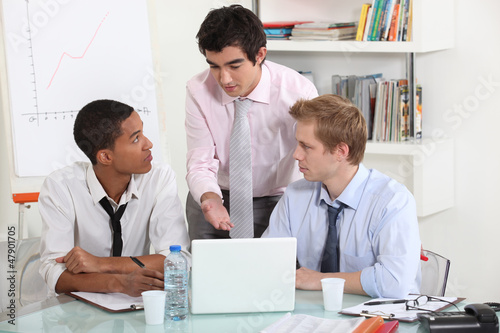 Three businessman working on a project.