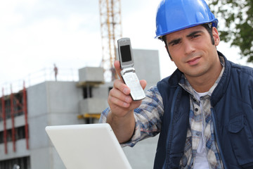 Foreman on construction site holding telephone