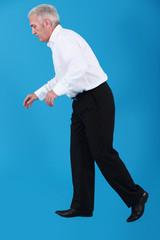 Businessman taking faltering steps