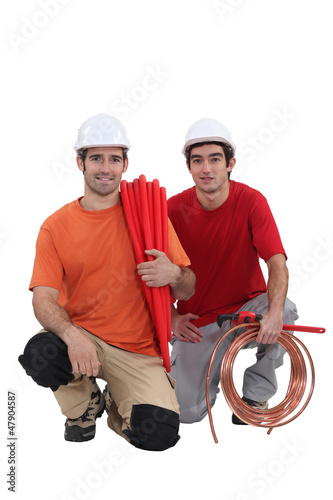 Kneeling tradesmen holding building materials and tools