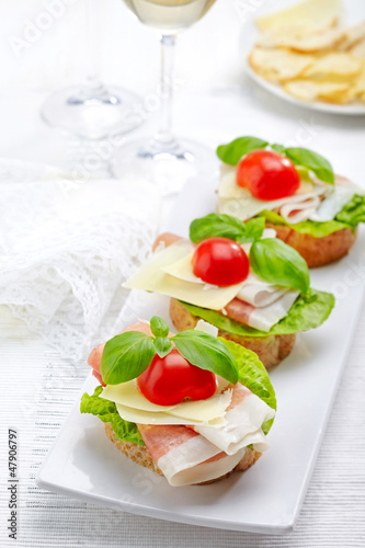 Sandwich with prosciutto, parmesan cheese and tomato