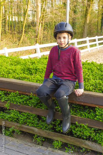 cute teenage  boy in helmet and boots for horse riding sitting n