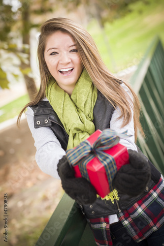 Pretty Woman with Wrapped Gift with Bow Outside