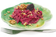 Beetroot salad with walnuts on green plate