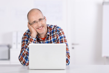 zufriedener mann mit seinem laptop