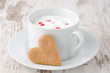 cup of hot milk decorated with sugar hearts and cookie