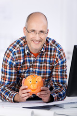 lächelnder mann mit sparschwein