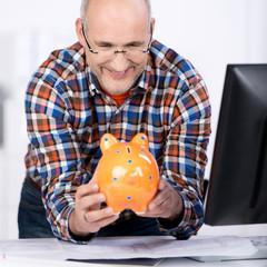 mann am schreibtisch schaut auf ein sparschwein