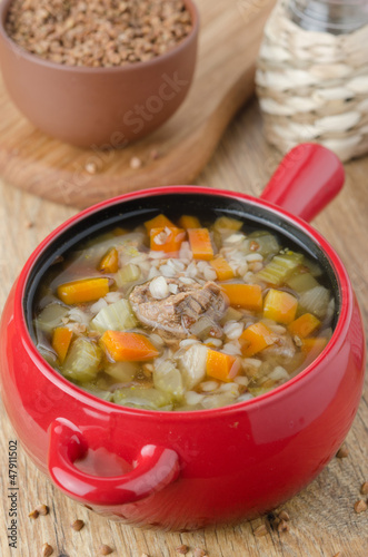 soup with beef and buckwheat in a red pot