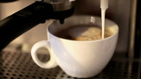 Foamy milk flows into a big white cup of cappuccino