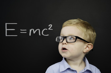 Smart young boy stood in front of a blackboard