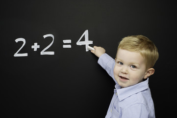 Smart young boy stood writing on a blackboard