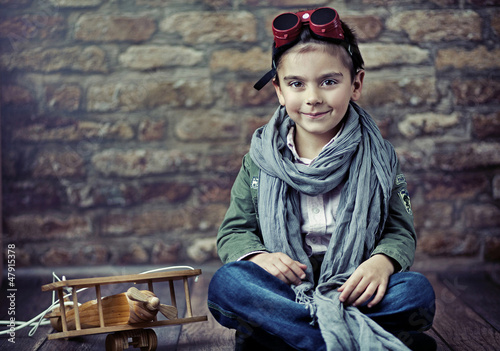 Cute smiling boy with wooden plane