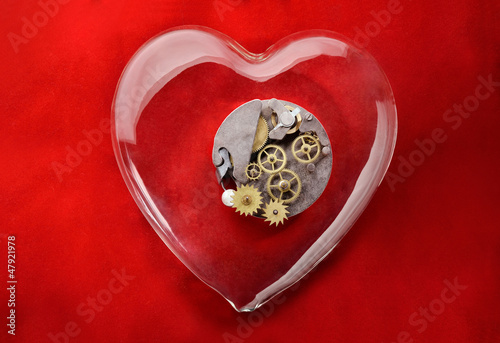Gear wheels inside glass heart with red background