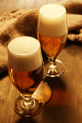 Glasses of beer on wooden table close-up