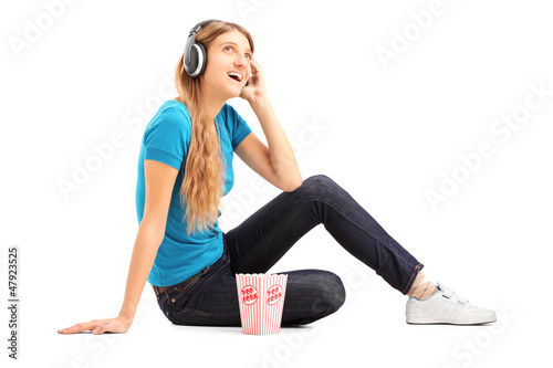 Blond female listening a music and eating popcorn