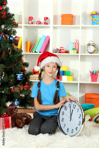Little girl holding clock near christmas tree