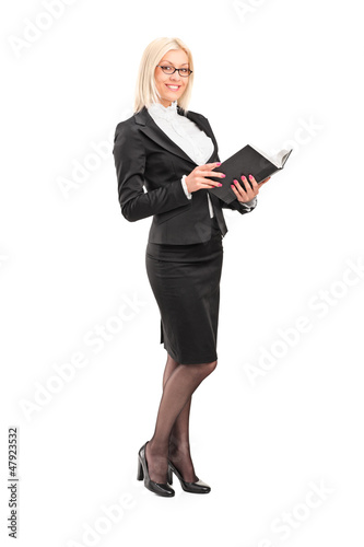 Full length portrait of a blond female teacher holding a book