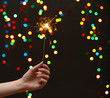beautiful sparkler in woman hand on garland background.