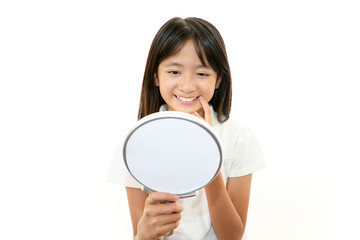 手鏡を持ち歯をチェックする女の子