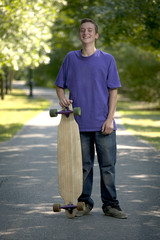 Young teenager holding his longboard