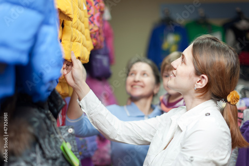 family chooses winter wear at clothes store