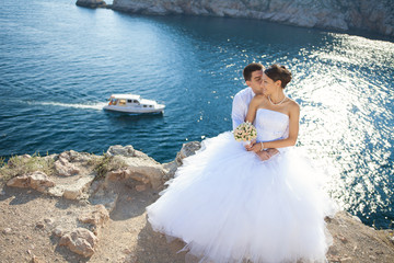 young bride and groom hugging on cliff background of blue sea