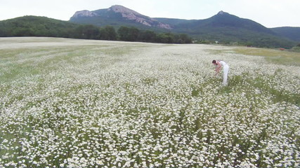 Woman in a field of daisies at blossoming season