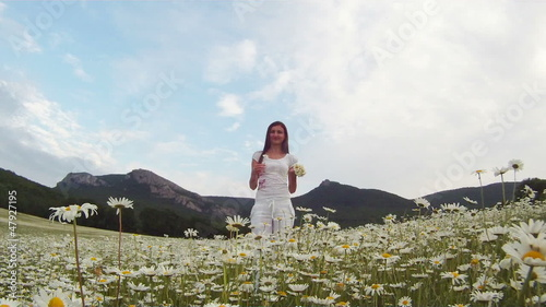 Woman picking the daisies and throwing them up in the air