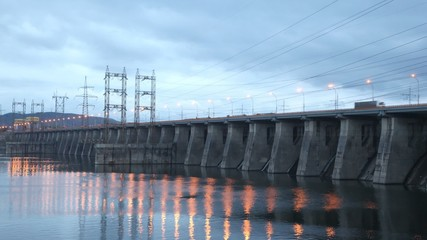 Cars go on bridge in night which is also spillway dike