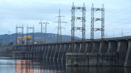 Cars go on bridge which is also spillway dike closeup