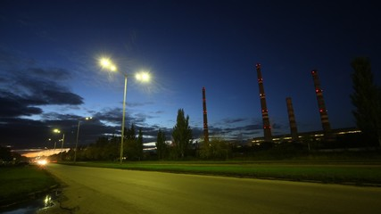 Cars go on highway in front of chimney shaft of manufacturing