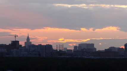 City stand against sky on sunset where sun hides at clouds