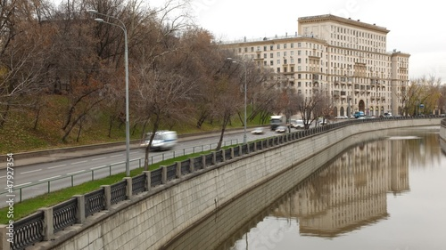 Cars go on river Jauza embankment in front of old building
