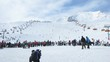 Crowd of people stand and wait turn in a zone of skiing