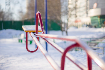 Kids red metal swings on winter playground covered with snow