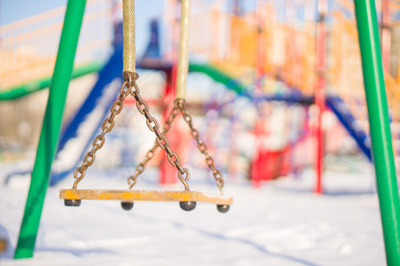 Kids chain swings on winter playground covered with snow